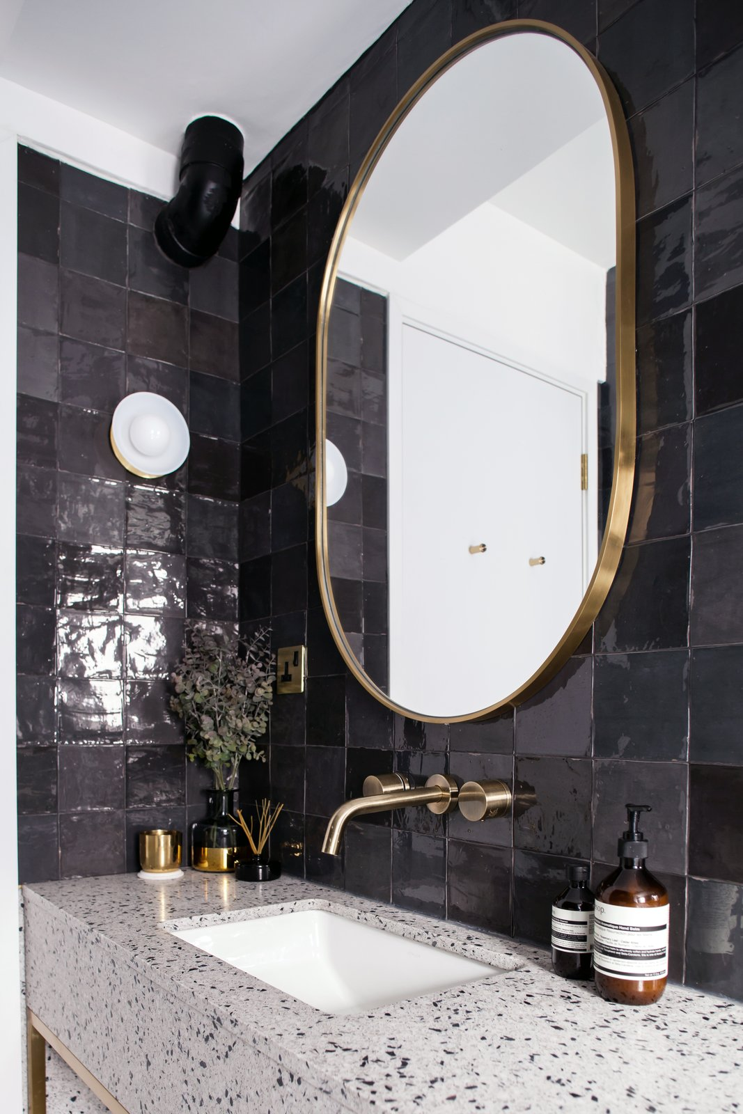 Bath Room, Terrazzo Floor, Alcove Tub, Wall Lighting, Stone Counter, Recessed Lighting, Drop In Sink, One Piece Toilet, and Ceramic Tile Wall Guest bathroom detail with terrazzo, dark grey tiles, and brass accents  Photos from Quarry Bay Residence