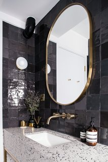 Guest bathroom detail with terrazzo, dark grey tiles, and brass accents