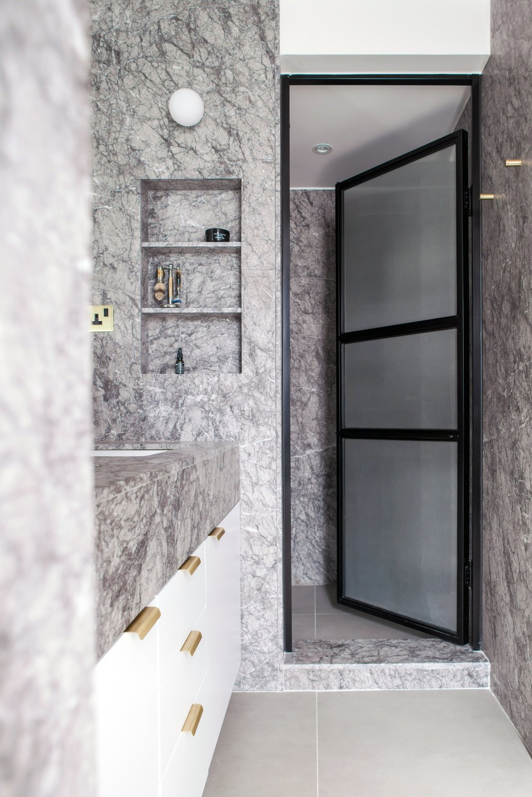 Bath, Marble, Wall, Marble, Enclosed, Ceramic Tile, Recessed, and Drop In Grey marble, white wood, black metal and glass doors, along with brass accents, creates a contemporary and calming master bathroom.  Bath Marble Enclosed Drop In Marble Photos from Quarry Bay Residence