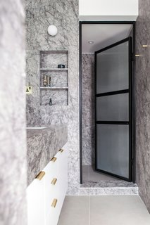 Grey marble, white wood, black metal and glass doors, along with brass accents, creates a contemporary and calming master bathroom.