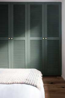 A muted green closet design adds a pop of color and sophistication to the guest bedroom