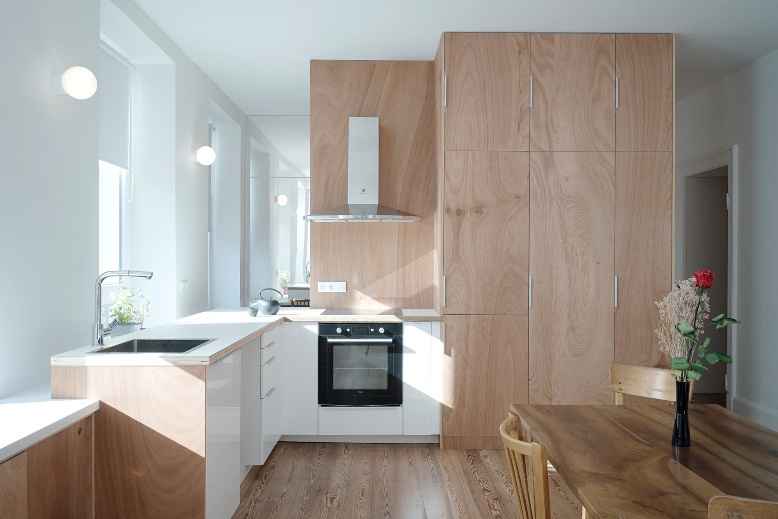 Kitchen, Medium Hardwood, Wood, Wood, Wall, Refrigerator, and Cooktops the kitchen is at the center of the living space  Best Kitchen Wood Refrigerator Wall Cooktops Wood Photos from Corner Apartment in Strasbourg, France