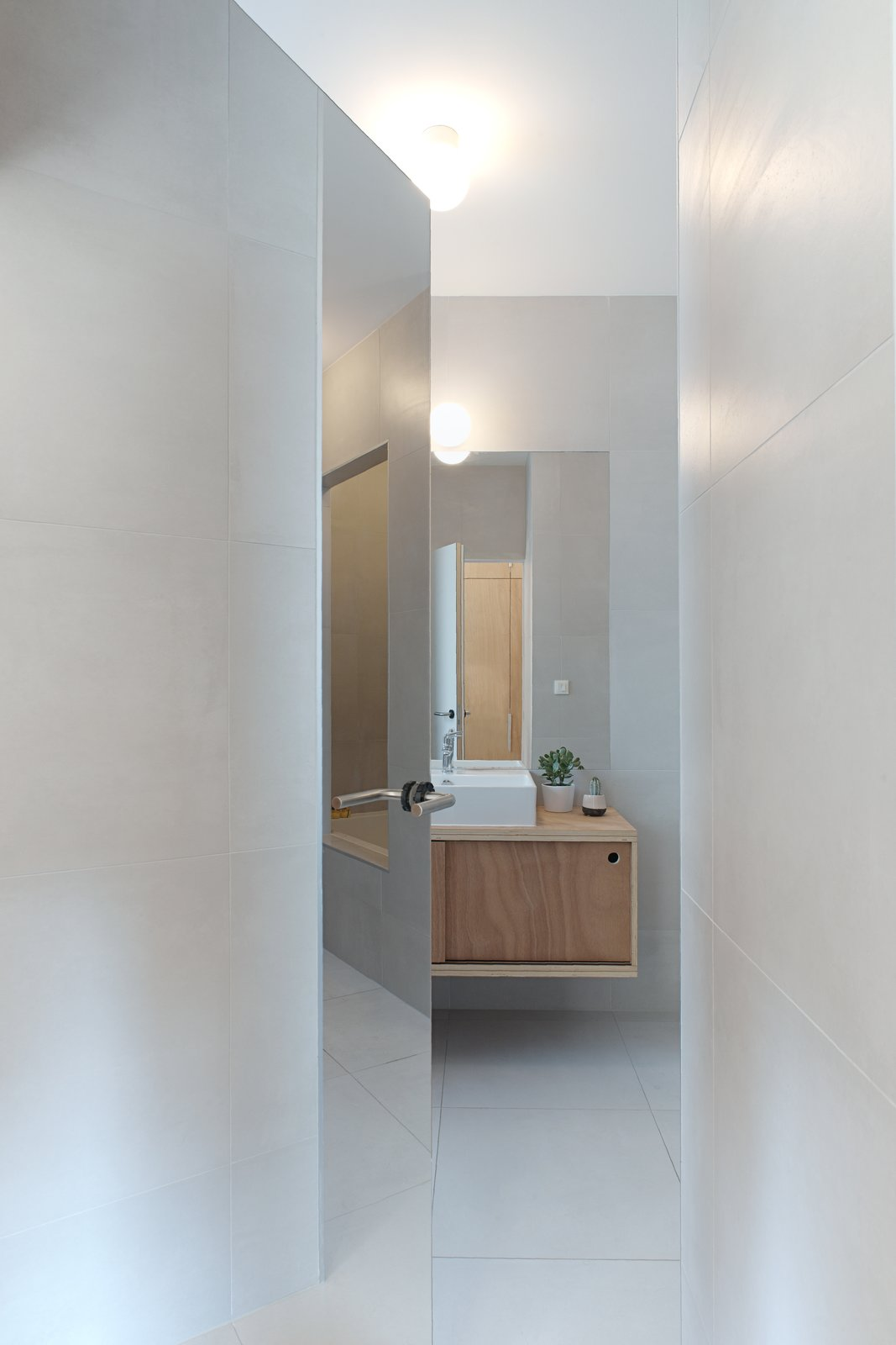 Bath Room, Ceiling Lighting, Wall Lighting, Ceramic Tile Floor, and Ceramic Tile Wall The mirrored door opens on the bathroom  Corner Apartment in Strasbourg, France by Dratler Duthoit