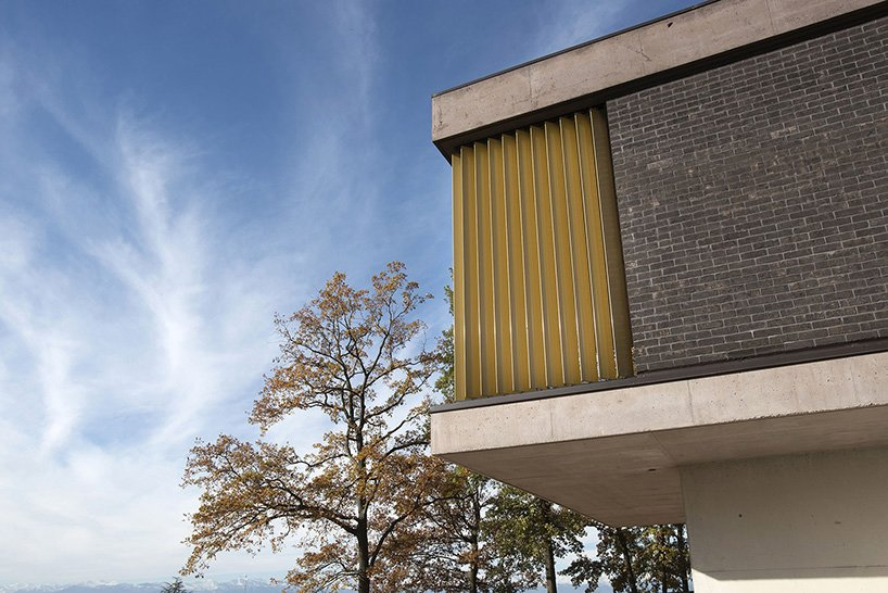 Exterior, House Building Type, Metal Siding Material, Concrete Siding Material, Flat RoofLine, Wood Siding Material, and Brick Siding Material Close view of the exposed concrete slabs , brick wall and aluminium louvers  Villa Rambo