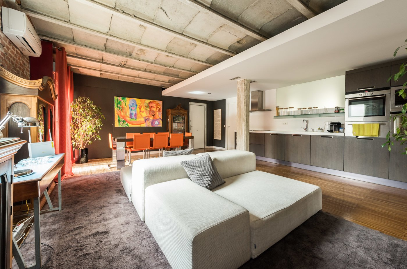 """Living Room, Medium Hardwood Floor, Sofa, and Chair The kitchen is incorporated into the main space. It's from Bontempi. In the background, presiding over the room, a painting painted by José Trapaga, entitled """"La trampa"""".  Echávarri house 100m2. Loft between gardens."""