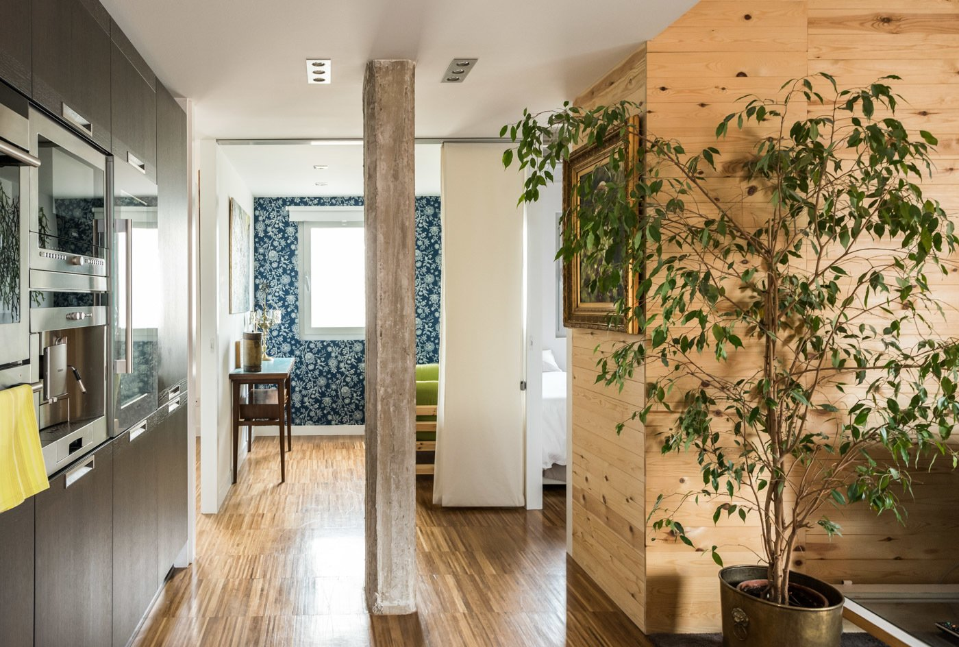 Office, Study Room Type, and Medium Hardwood Floor  In the background are the bedrooms. On the right with a wall clad in pine wood, on the center with a sofa bed in a small multipurpose space, and on the left, the master bedroom.  Echávarri house 100m2. Loft between gardens.