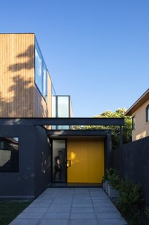 The exterior walls on the first floor of Virginia House by 2712 / Asociados are painted in a dark, neutral color that contrasts with the bright illuminated interiors and sunny yellow front door.
