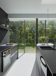 The kitchen in 1220 E. 12th Street House features floor-to-ceiling windows that look out on a serene grove of oak trees. The project was designed by Studio 804, a graduate student architecture and design program led by Dan Rockhill at the University of Kansas.
