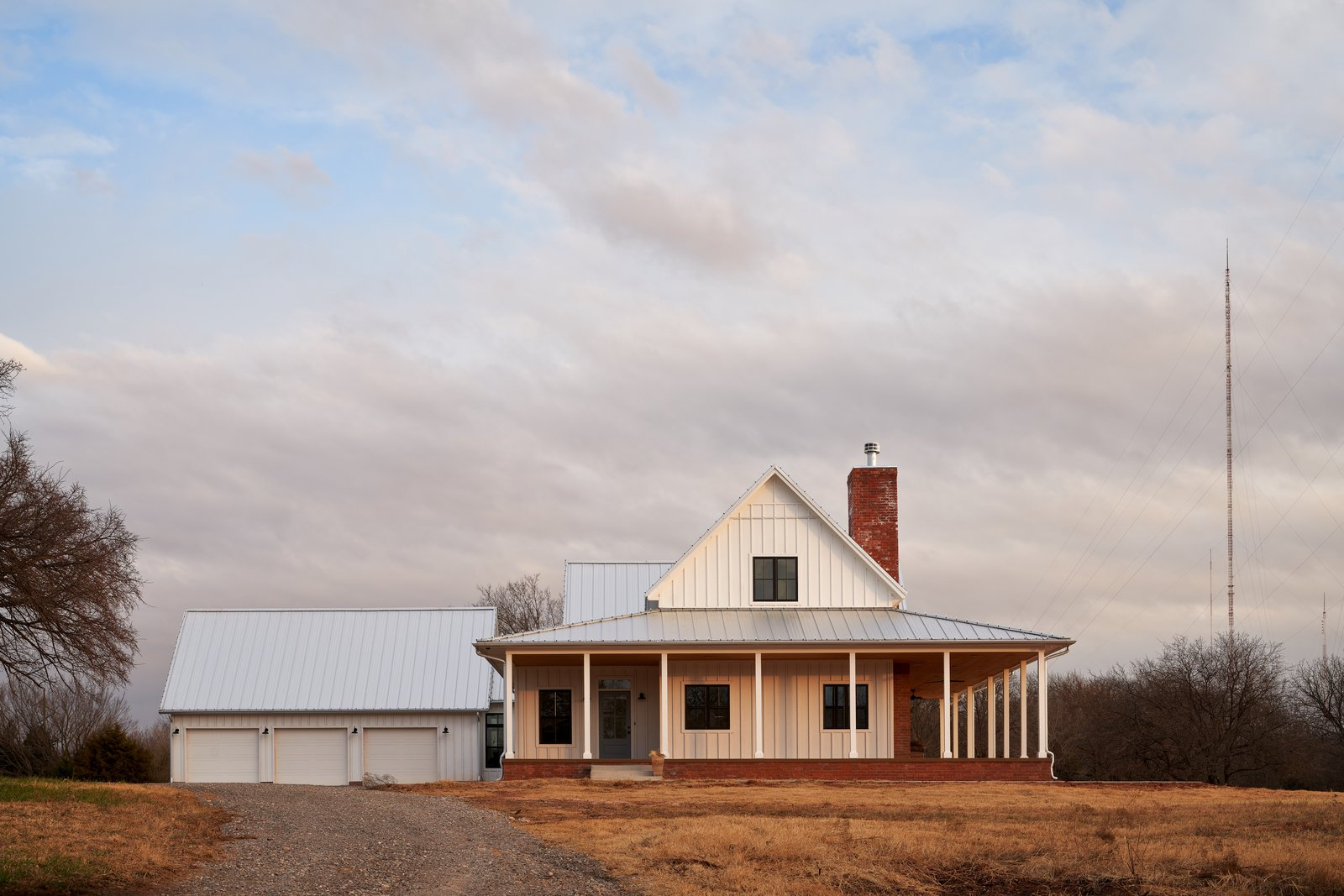 Exterior, Wood Siding Material, Gable RoofLine, House Building Type, and Metal Roof Material After passing through a small grove of trees at the front of the property, the drive turns toward the front view of the farmhouse.   OKC Farmhouse by Scharbach Workshop