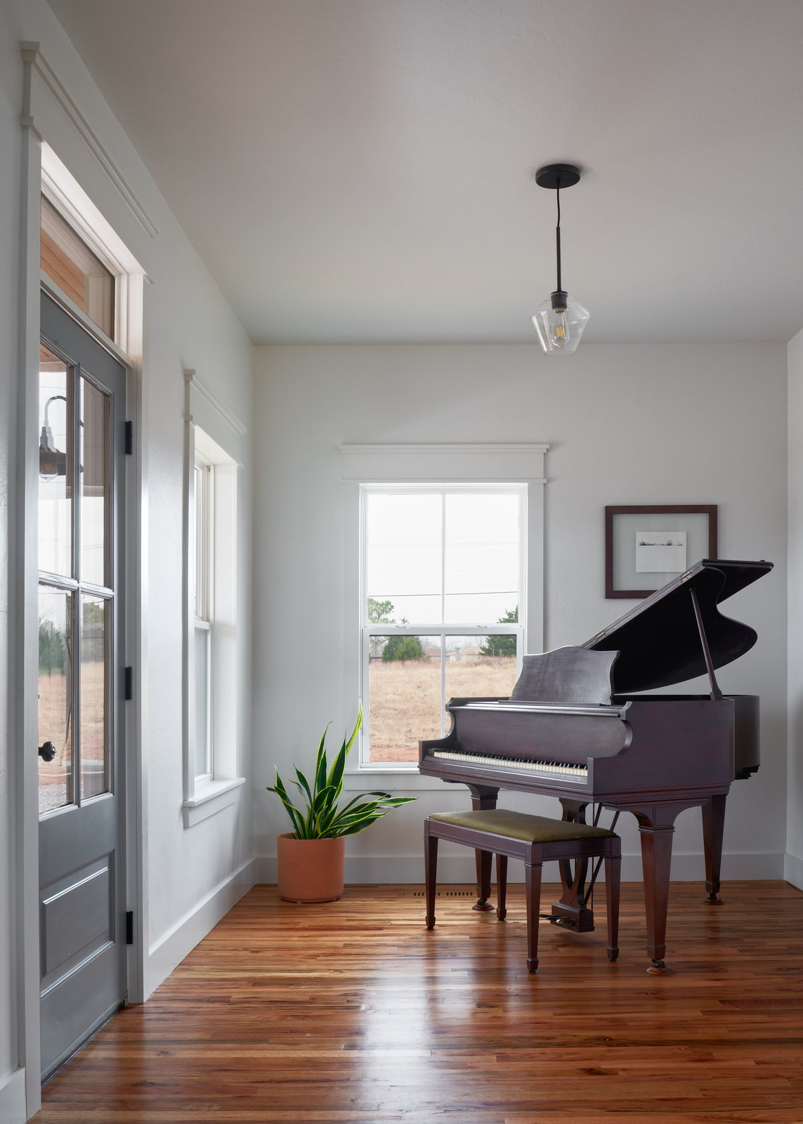 Living Room, Pendant Lighting, and Medium Hardwood Floor The front entry was designed with a family heirloom baby grand piano in mind.  OKC Farmhouse by Scharbach Workshop