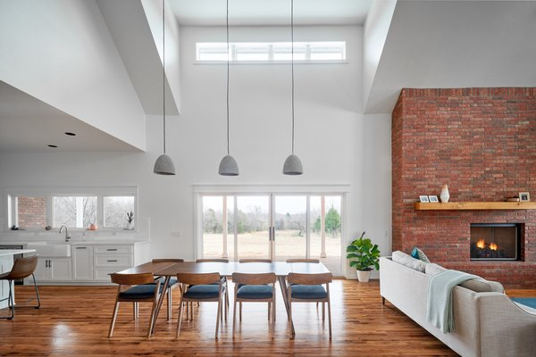 The dining room of OKC Farmhouse by Scharbach Workshop features high ceilings, distinctive pendant lighting, and connects to the other areas of the house in an elegant way.