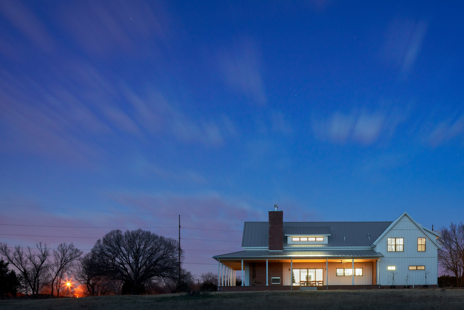 Exterior, House Building Type, Brick Siding Material, Gable RoofLine, Wood Siding Material, and Metal Roof Material Back of the House at Dusk  OKC Farmhouse by Scharbach Workshop