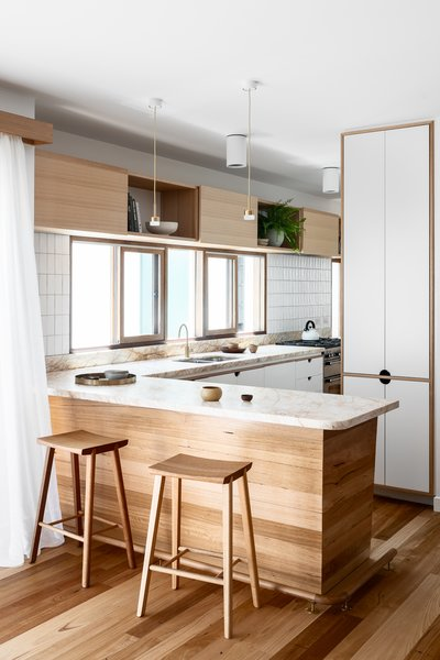 A galley-style kitchen is tucked away at the side of the house, but accessible from the main living areas.