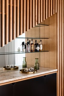 Happy hour has never looked so good. The home's wet bar receives stylish treatment with an asymmetrical facade and mirrored background.