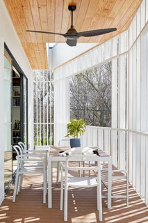 Finished with a ceiling and dining table set, the second-floor patio is an optimal entertaining space.