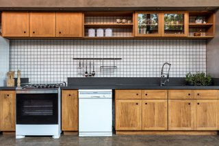 The kitchen functions similarly to those in farmhouses, since the appliance run is tucked against one wall, and the nearby dining table can be used for additional prep if needed.