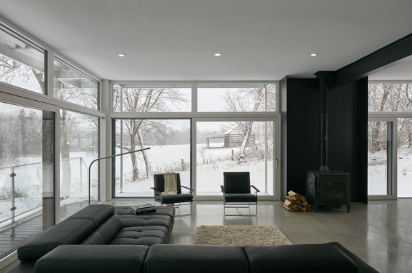 The main level living space of Industrial Farmhouse by Christopher Simmond Architect Inc. is a transparent social hub for viewing the rural landscape. The house is situated to optimize views, as well as protect occupants from the blazing summer sun and stiff winter winds.