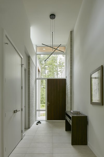 Christopher Simmonds Architect designed both the interior and exterior of Ravine Bungalow with a simple material palette. Masonry wraps into the entrance hallway, further emphasizing the connection between interior and exterior.