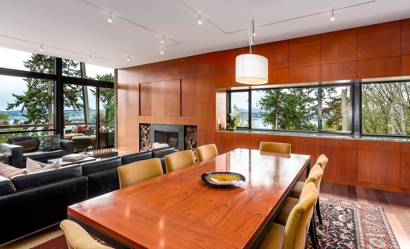 Dining Room The rectilinear floor plan places all of the living spaces in a row. The walls are paneled in rich Brazilian cherry wood, and they house ample built-in storage.  Photo 4 of 8 in A Cantilevered Bainbridge Island Home Set Atop a Historic Bunker Lists For $1.73M from Stunning Steel-Frame Construction Cantilevered atop Historic Bunker For Sale