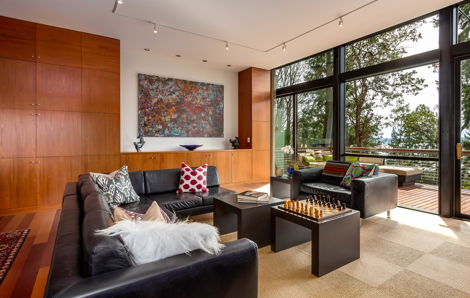 Living Room The living room has a full-height wall of windows, and it opens to a deck with spectacular views of the forested surroundings.  Photo 3 of 8 in A Cantilevered Bainbridge Island Home Set Atop a Historic Bunker Lists For $1.73M from Stunning Steel-Frame Construction Cantilevered atop Historic Bunker For Sale