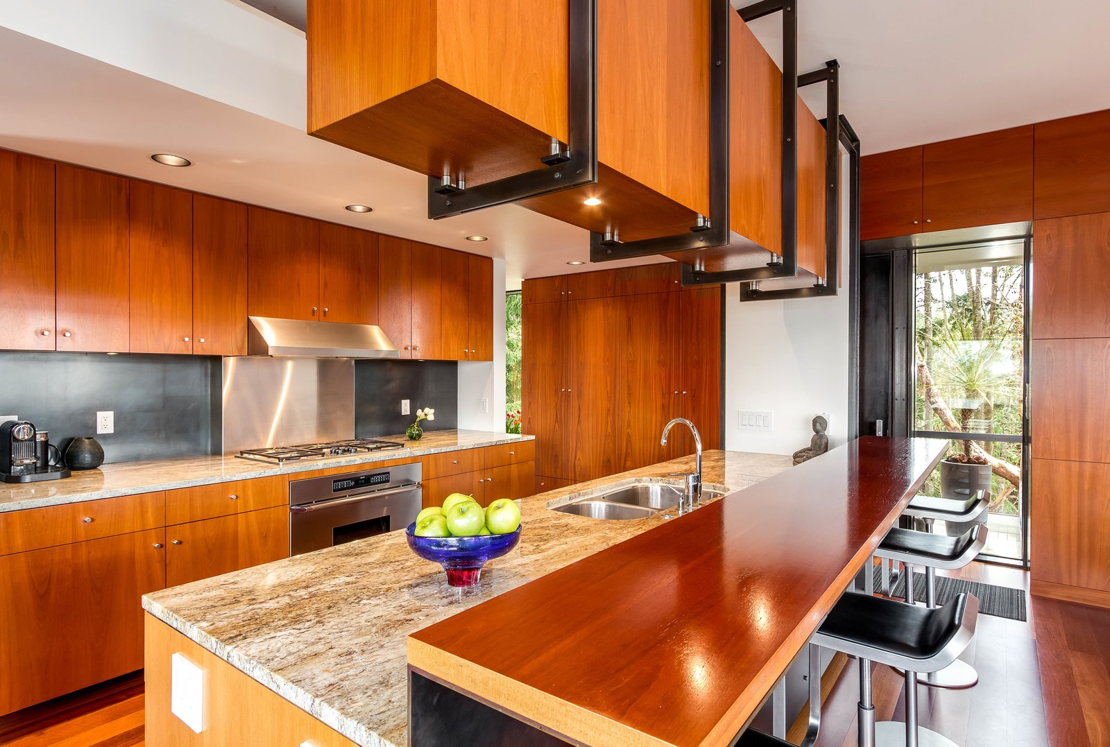 Kitchen The modern kitchen features high-end finishes and breakfast bar seating.   Photo 5 of 8 in A Cantilevered Bainbridge Island Home Set Atop a Historic Bunker Lists For $1.73M from Stunning Steel-Frame Construction Cantilevered atop Historic Bunker For Sale
