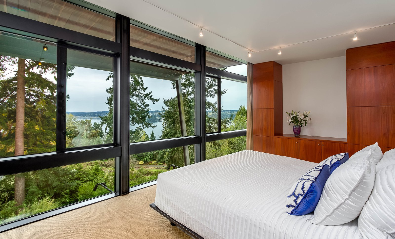 Bedroom The master bedroom features amazing views and built-in storage.  Photo 6 of 8 in A Cantilevered Bainbridge Island Home Set Atop a Historic Bunker Lists For $1.73M from Stunning Steel-Frame Construction Cantilevered atop Historic Bunker For Sale
