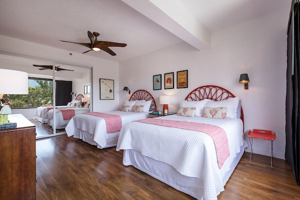 Bedroom, Accent Lighting, Laminate Floor, Bed, Dresser, Night Stands, Medium Hardwood Floor, Wall Lighting, Ceiling Lighting, and Storage Double queen guest bedroom with pops of coral and Hawai'ian decor.  Maui Modern, Budget-Luxury Remodeled Vacation Rental