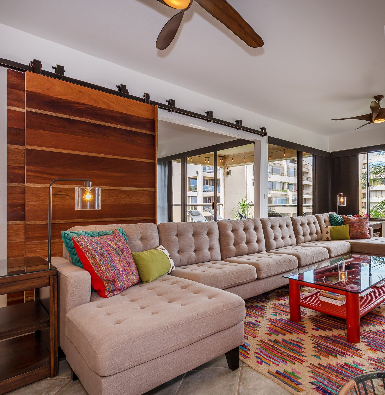 Living Room, Coffee Tables, End Tables, Sectional, Ceiling Lighting, Floor Lighting, and Ceramic Tile Floor Custom-built mahogany doors make a statement in the living room & give maximum privacy.  Maui Modern, Budget-Luxury Remodeled Vacation Rental