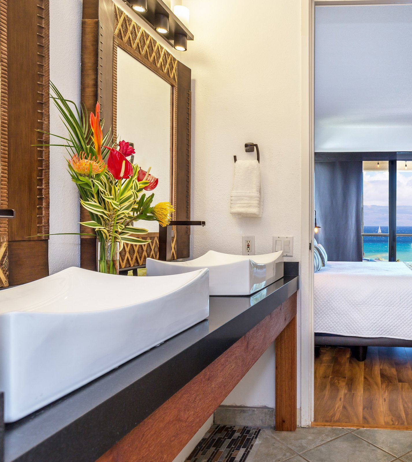Bath Room, Wall Lighting, Granite Counter, Open Shower, Vessel Sink, Concrete Wall, Full Shower, One Piece Toilet, Soaking Tub, and Ceramic Tile Floor Custom vanity with vintage Hawai'ian mirrors bring together the old and the new.   Maui Modern, Budget-Luxury Remodeled Vacation Rental