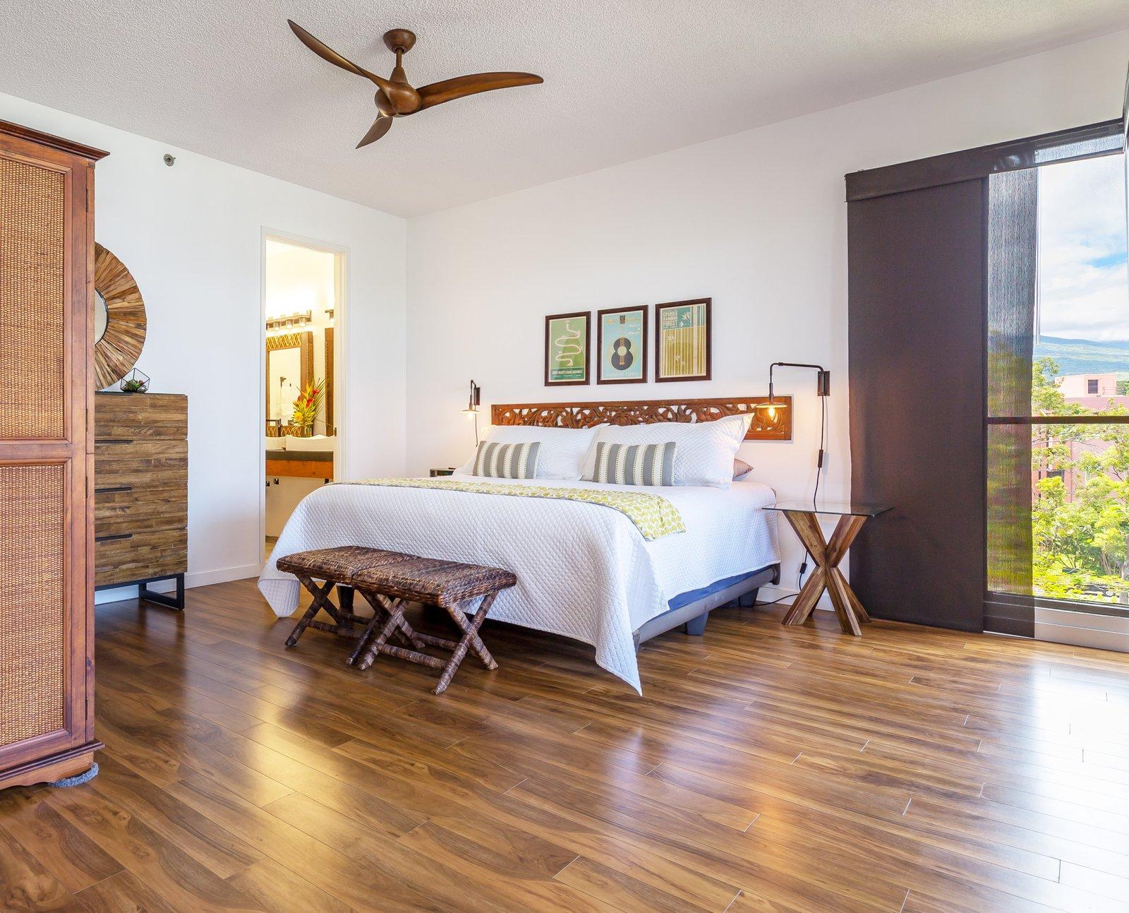 Bedroom, Accent Lighting, Night Stands, Storage, Dresser, Medium Hardwood Floor, Bench, Bed, Laminate Floor, and Wall Lighting Master bedroom with antique Balinese headboard.   Maui Modern, Budget-Luxury Remodeled Vacation Rental