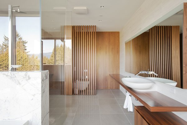 Evoke International Design prioritized views of the heavily wooded lot surrounding the Point Grey residence, shown especially on the upper floors. Nearly every room, including this wood bathroom, features large windows to drink in nature.