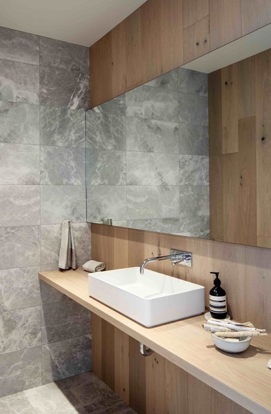 Grey marble and oak panels line powder room walls.