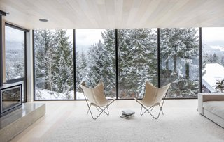 Framed snowy views from upper floor to ski hills beyond through wall to wall full height windows