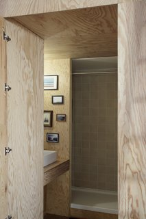 The bathroom is fitted with pine plywood and minimally decorated with framed photographs.