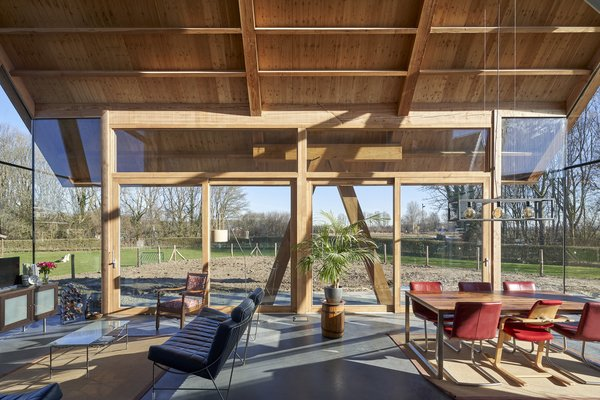 """A gabled roof home in Werkhoven, a Dutch village in the province of Utrecht, takes the form of a modern barn with a twist—split down the middle from the peak, half of the exterior is floor-to-ceiling glass to take advantage of the views. """"The transition from inside to outside, and vice versa, is always important in our designs,"""" says architect Ruud Visser."""