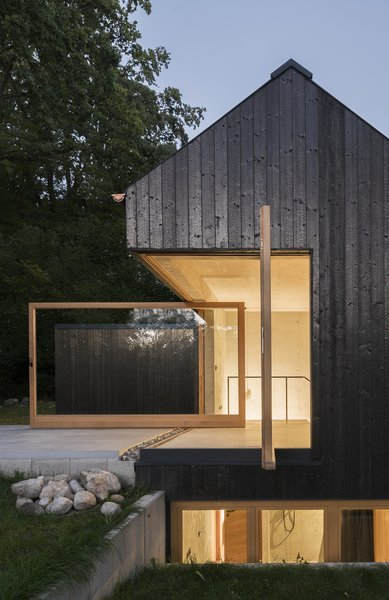 The dark facade that covers Das Schwarze Haus has been preserved through carbonization, instead of through chemical treatment. Buero Wagner's design sits quietly in the countryside, a slender volume rising out of the trees.