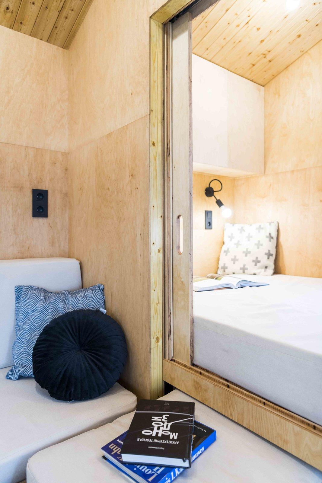 Bedroom, Wall Lighting, Bed, and Light Hardwood Floor Sliding door to separate the bedroom niche  KOLELIBA Family Tiny House