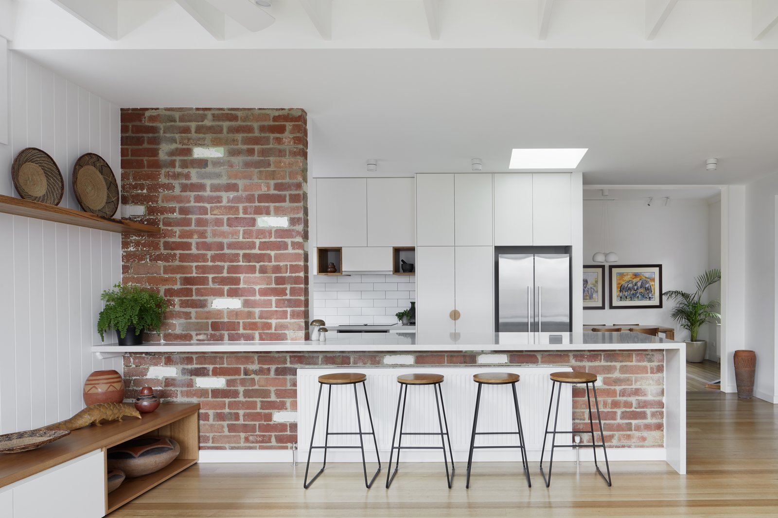 Kitchen, Engineered Quartz Counter, Track Lighting, Cooktops, Refrigerator, Ceramic Tile Backsplashe, Light Hardwood Floor, Subway Tile Backsplashe, and White Cabinet Existing brick wall is reinstated with recycled brick and opened to form connection between kitchen and  living   Preston 1