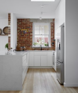 Galley kitchen with existing brick wall celebrating original fabric of the house.