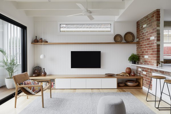 Living room with low built in units maximises sense of height to new living space, while shelves provide ample spaces to display client's wonderful collection of African artefacts