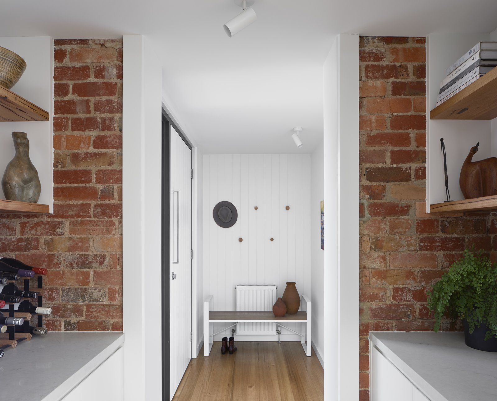 Hallway and Light Hardwood Floor Texture of existing brick to the kitchen and v-grooved timber lining to the entry provide warmth with fresh white maximises light throughout.   Preston 1