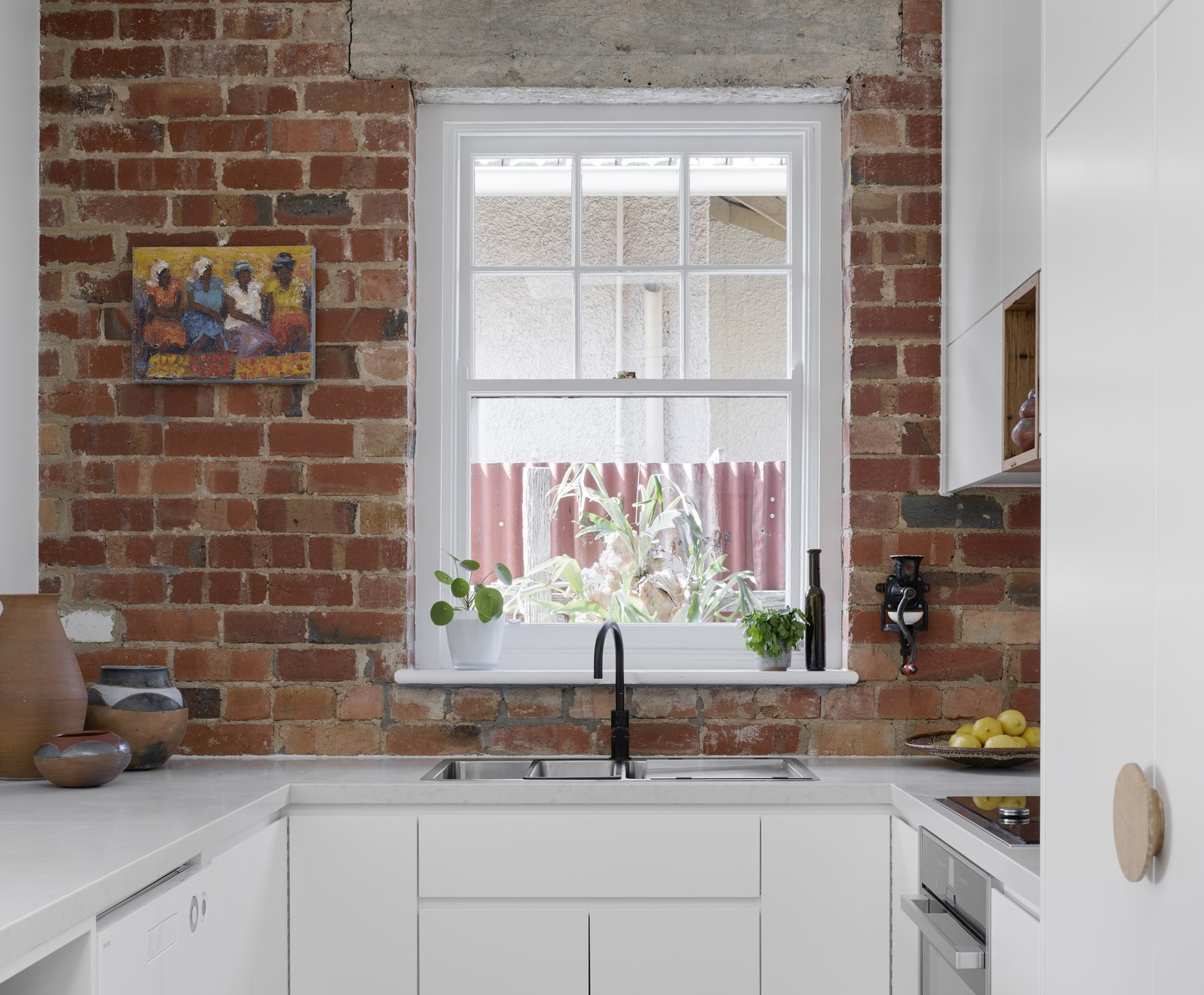 Kitchen, Engineered Quartz Counter, Brick Backsplashe, Range Hood, Dishwasher, White Cabinet, and Cooktops The clean line of Caesarstone bench contracts with the exposed textured brickwork of the original building fabric , now a feature of the kitchen    Preston 1