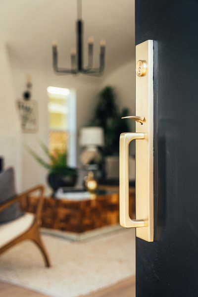 An elongated escutcheon, long handle pull, and thumb-operated latch give this exterior handleset a striking, modern style.