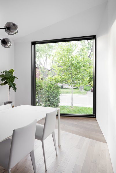 View from dining room looking towards front yard. The white washed white oak folds up completing the front aperture  that repeats itself on the exterior.  Dining Chairs: Kristalia Bikappa Chair Dining Table: Kristalia Nori Extendable Table