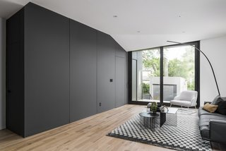 View from the kitchen looking towards rear yard and mudroom.  Hidden doors conceal access to the powder room and the mudroom and its access to the rear deck, yard and parking, placing greater priority on the relationship between interior and exterior living spaces.   Chair: Bonaldo Blazer Lounge Chair Lamp: Cattelan Italia Lampo