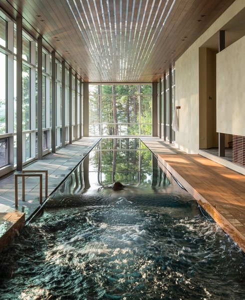 The main attraction of the Whitefish Poolhouse & Gallery is the 75-foot-long lap pool. The space, designed by CTA Architects, also features wraparound windows for stunning views of the lush forest.