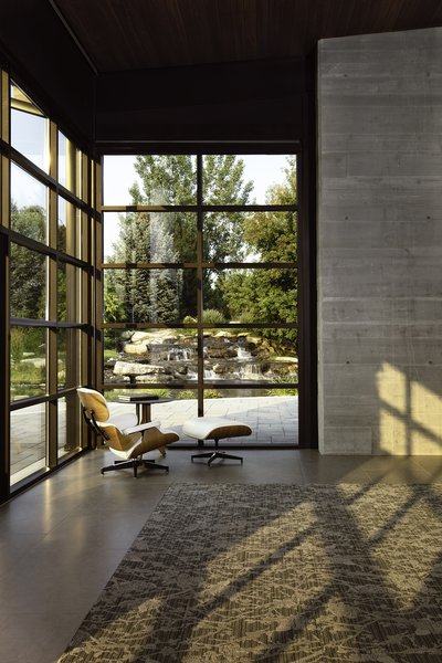 An Eames lounge chair overlooks a cascading waterfall outside the Thompson Lake House. Architect CTA   Cushing Terrell designed the home to feel flexible and customizable.