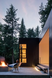 The patio of Collector's Retreat  by Heliotrope Architects allows the homeowners to gaze out into a sea of trees.