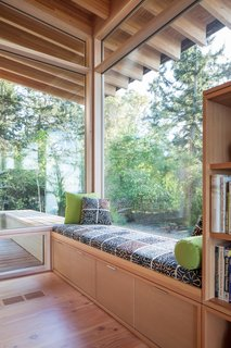 This cozy corner of Bunny Lane by Heliotrope Architects is perfect for curling up with a good book and soaking in the forest views.