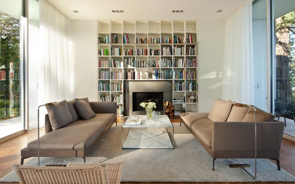 The living room has reflected sofas and plenty of shelves for the library of books